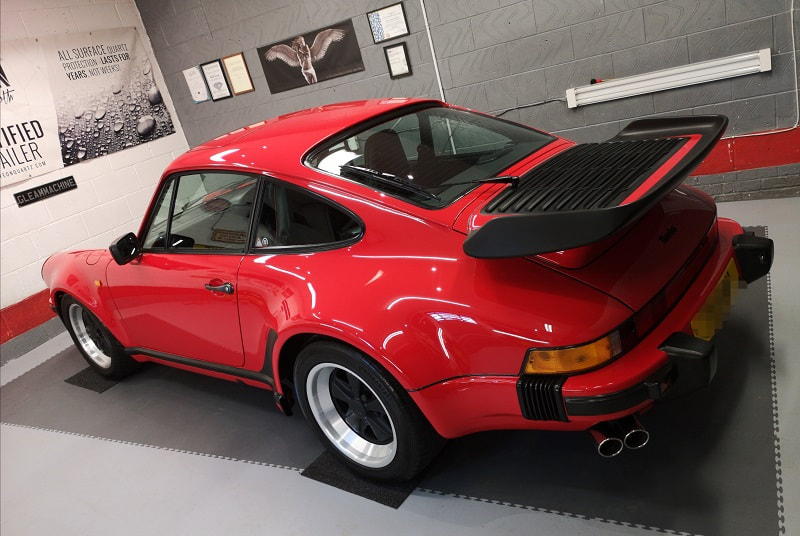 Guards red Porsche 911 car awaiting collection from detailing studio in Essex